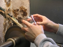 To hand cut crystal, the artisan looks through the glass, at the cutting wheel